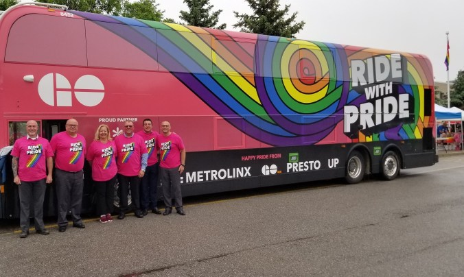 Metrolinx employees line up in front of a rainbow coloured GO bus.