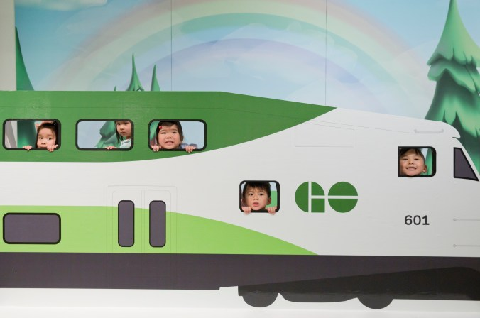 Children's faces are seen looking out of the windows of a small GO train display.
