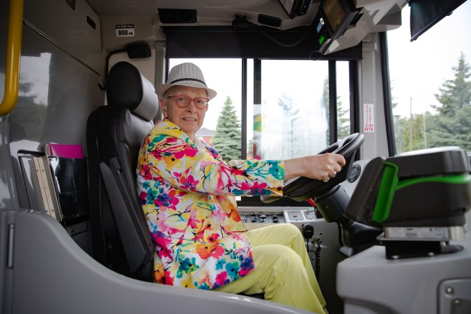Russell poses as he has his hands on the wheel of a GO bus.