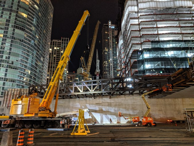 Large crane moves a big piece of metal into place over the tracks.