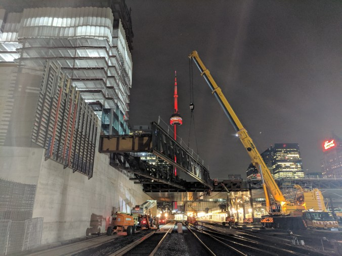 large yellow crane lifts big piece of metal into place with the lit up CN Tower in the backgound.