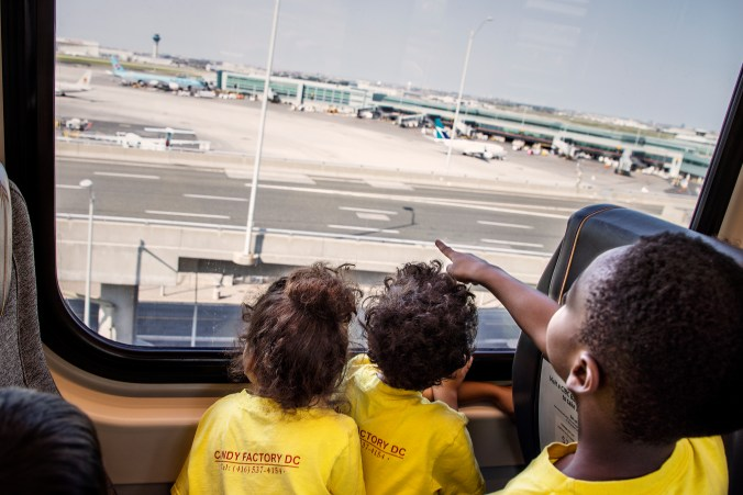 Children point to planes parked at the airport.