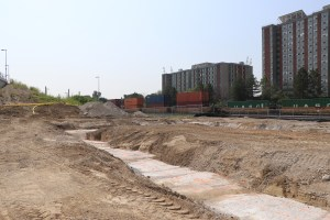 Construction continues as freight trains roll by on the adjacent train tracks.