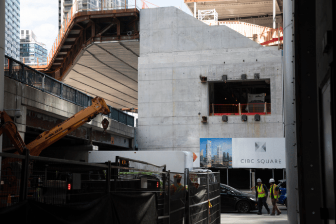 Workers walk past a square in a building that the bridge will be connected to.