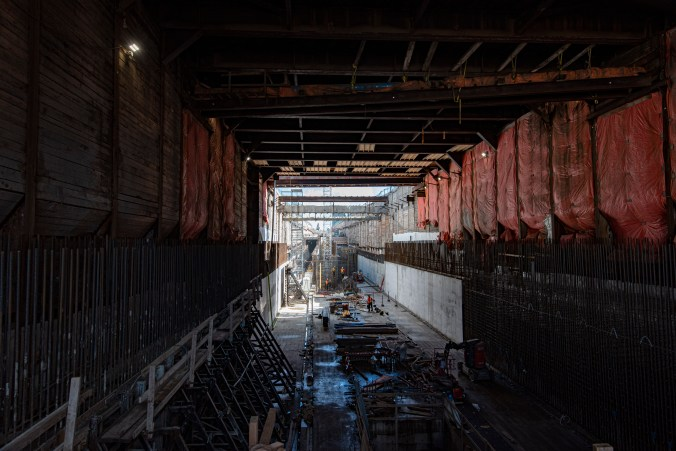Crews work deep in the concrete tunnel. Light is seen at the far end.
