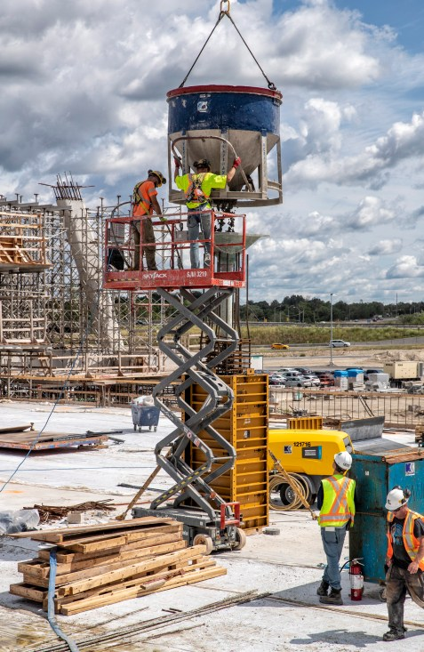 Construction workers lower a concrete bucket into place with use of a sky jack.