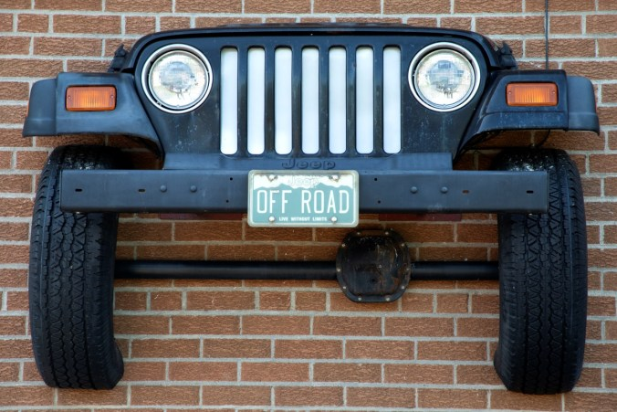 The front of a jeep is hung on a brick wall.