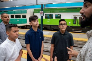 Adam Diz, Damon Kuarsingh, and Humza Choudhry stand on a platform at Union Station with Metrolinx staff