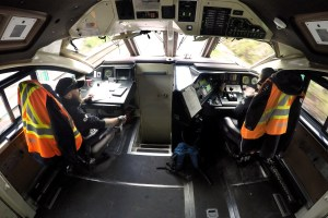 The image shows the inside of the cab of a GO train, looking outside.