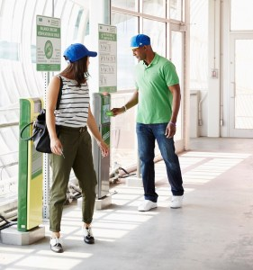 Man and woman walking in a corridor, the man stops to tap his PRESTO card.