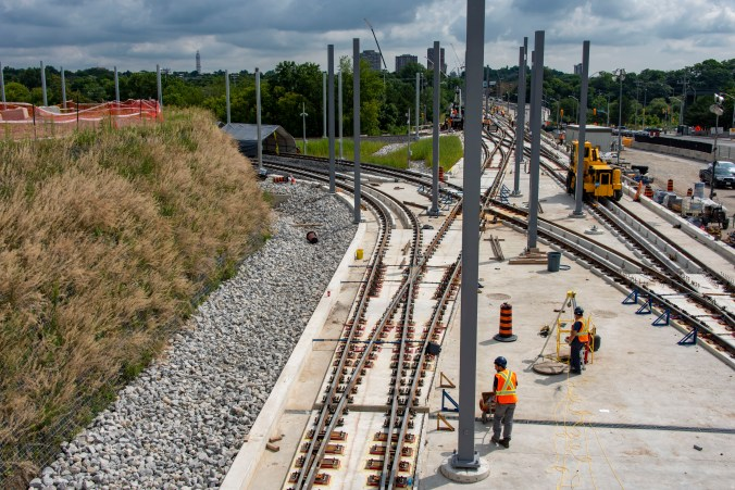 Men work on a section of track, which peels off into two directions.