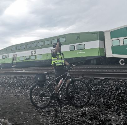 A team member waves at a passing GO train.