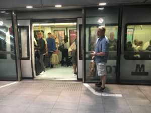 A man stands close to a train, as others wait to go.