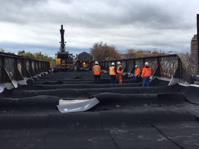 Crews work on a bridge, as heavy machinery moves nearby.