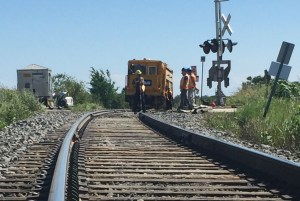 Image shows a rail line leading up to crews working.