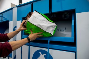 A person puts donated clothing into one of the donated bins.