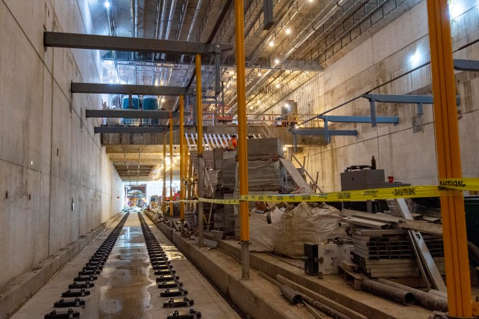 A look at track level, with concrete walls and construction safety tape looped around metal poles.