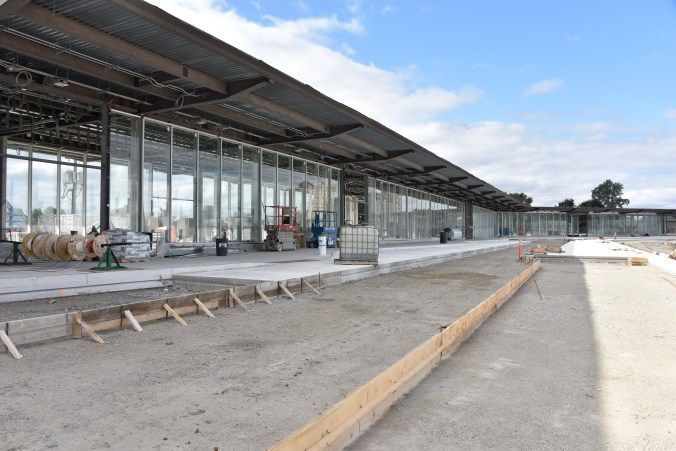 Outside a partially completed station, new concrete and pavement wait for next stages.