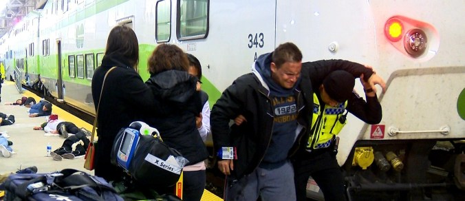 First responders tend to volunteer actors on the GO platform at Union Station during the emergency exercise.