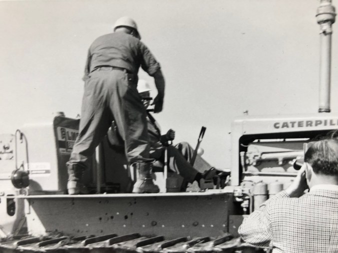 Two men sit on a tractor as one prepares to move it forward.