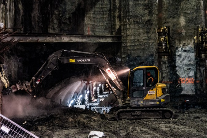 An earth mover digs into dirt, with a tunnel just behind.