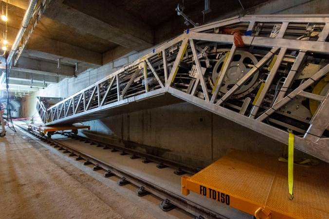 A large escalator sits on two small rail cars, inside the LRT tunnel.