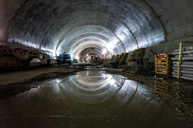 Image shows a puddle of water reflecting the top of the concrete tunnel.