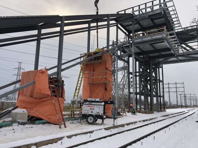 Image shows the new structure, including wrapping to help protect work from the elements.