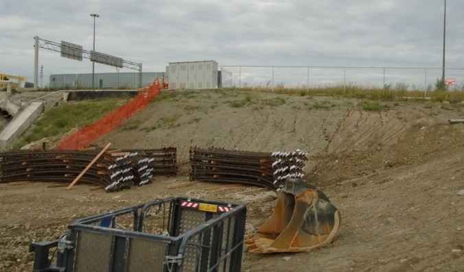 Iron girders wait on the ground at the site.