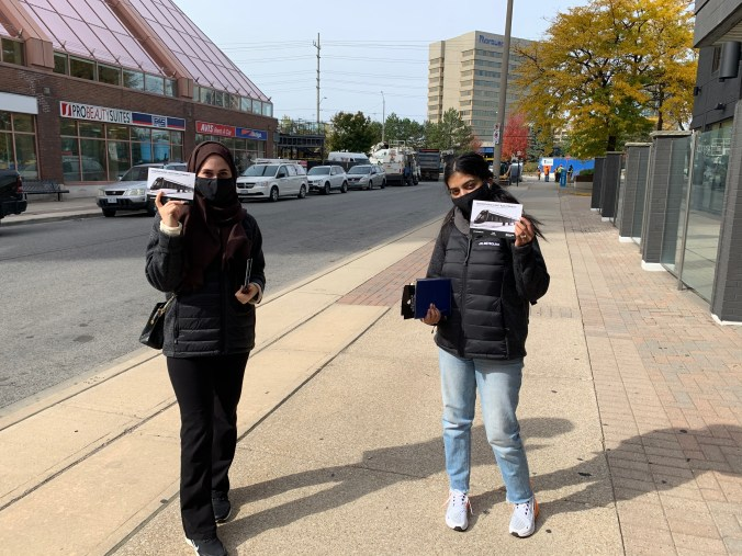 Two canvassers hold up information cards.
