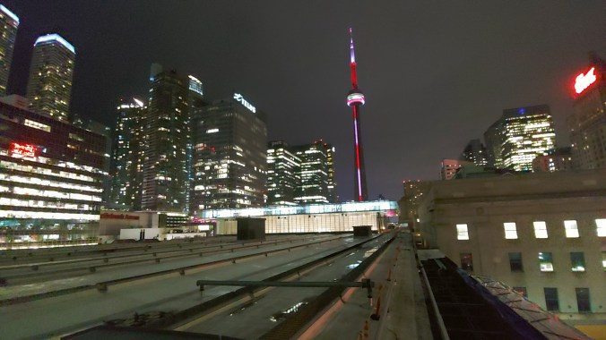 Union Station is lit up against a dark sky, with nearby office buildings also bright.