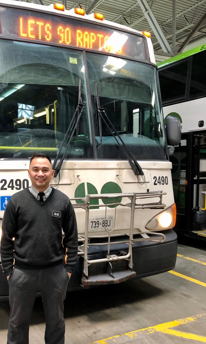 Imag a GO bus.e of Bryan in front of a bus.