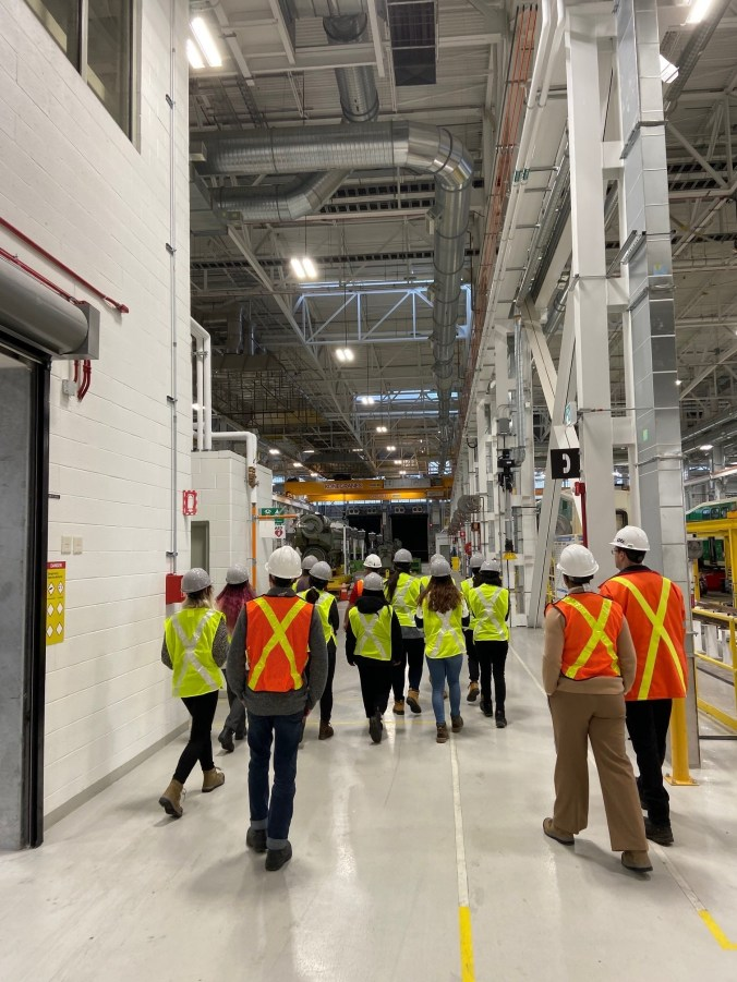A group walks through the inside of a large maintenance facility.