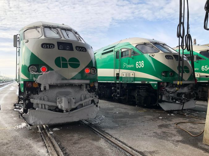 Image shows two GO trains, parked side by side in the cold.