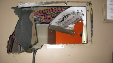 Image shows a wall with a large chunk taken out. Wiring can be seen inside.