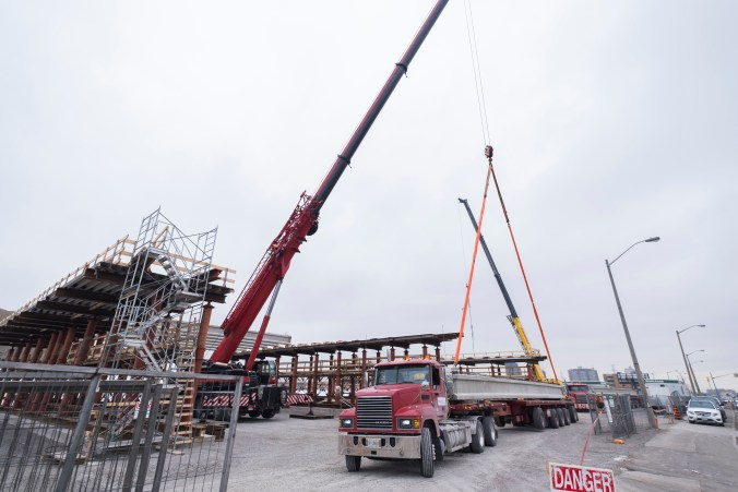 A crane lifts one of the large girders off of a truck.