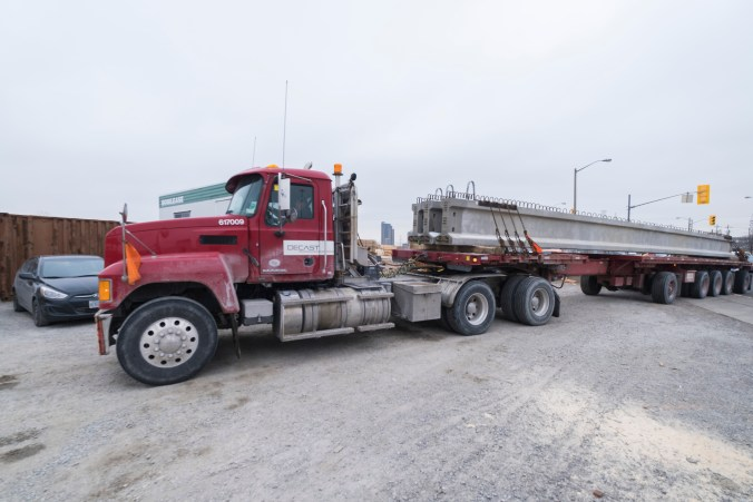 A truck hauls in large concrete girders.