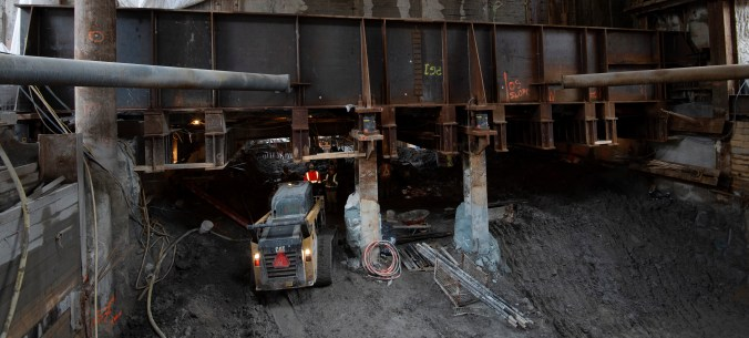 A tractor moves under a large girder.