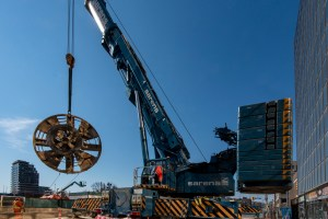The 6-metre long cutter head from one of the tunnel boring machines is lifted from deep underground.