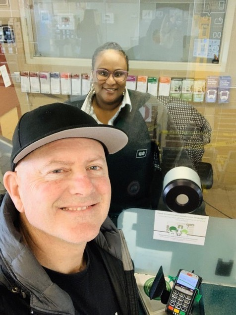 Sgt. Chris McCann poses for a selfie with a GO transit station attendant with the plexiglass shield between them