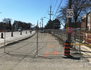 Construction fencing installed in one lane of traffic as construction happens in the roadway
