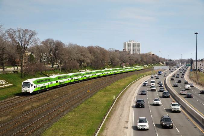 A GO Train moves along the Lakeshore West line beside the gardiner