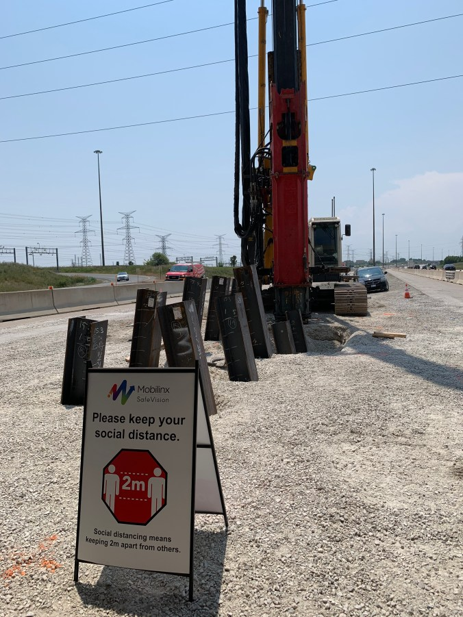 A sign reminding workers to keep two metres apart stands in front of a piece of machinery.