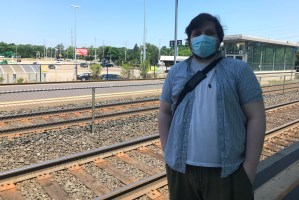 photo of a man in a medical mask standing on a GO Train platform