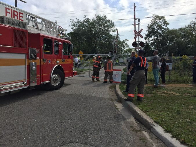 Fire crews and trucks are seen on a road.