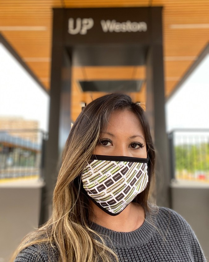 A woman wears a face covering on the UP Express platform.