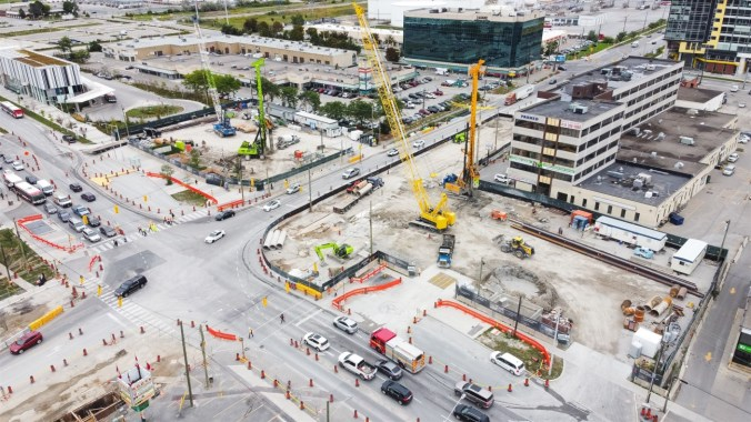 Image shows a construction site, looking down on large cranes.