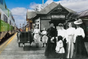 Image shows a meld of an historical photo of people on a platform with a GO train pulling up.
