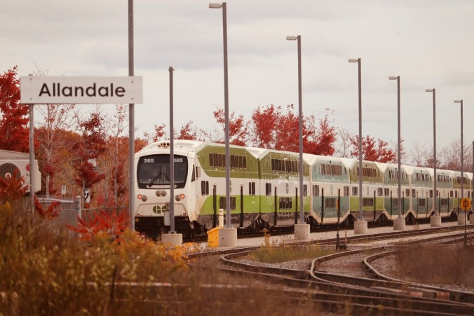 A GO train moves along tracks, with fall colours nearby.
