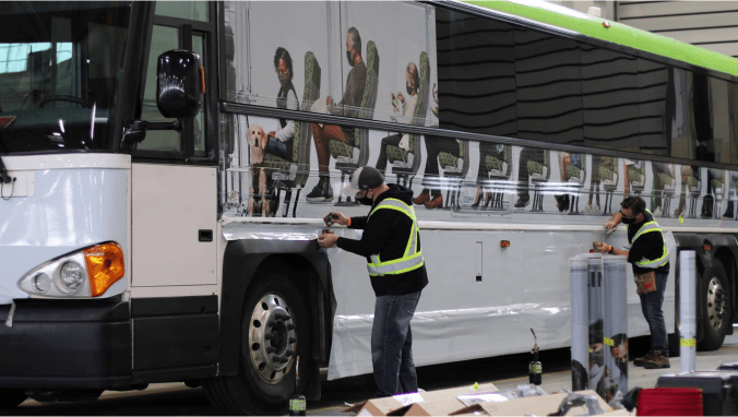 workers apply the bus wraps to a GO bus